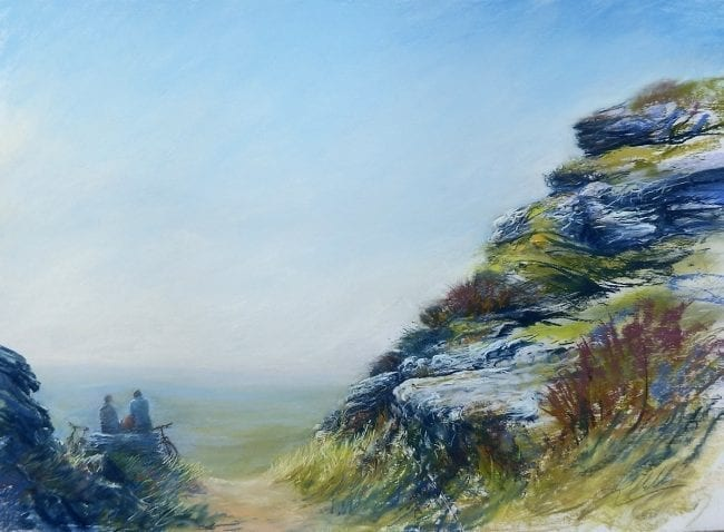 A pastel painting of the rocky landscape of Dartmoor in Devon. It shows two cyclists sitting on a rock, who have stopped for a rest at the top of a climb, There is a high rocky outcrop towering up next to them, and they are gazing into the hazy blue distance. Their bicycles are leaning against the rock.